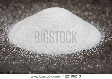 Pile of white sugar on a black cutting board with a selective focus around the edge of the pile