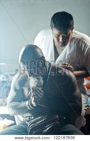 NAKHON CHAI, THAILAND - MAR 23, 2013: Master makes traditional Yantra tattoo to caucasian man during Wai Kru Master Day Ceremony in Wat Bang Pra in Nakhon Chai, Thailand.