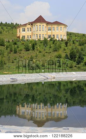 Altaiskoe, Russia - August 01, 2013: Cottage is reflected in the spring lake. Kennel Arboretum Blooming Valley.