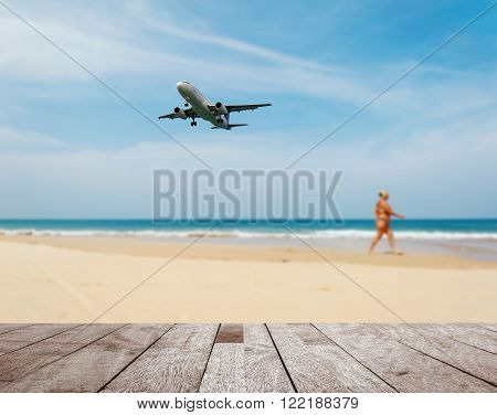Wood table top on blurred blue sea and white sand beach with some people and plane, Can be used for montage your products