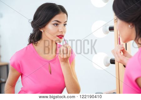 Attractive young woman with lip brush looking at the mirror and applying red lipstick to her lips