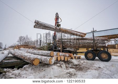 Sawmill in wintertime. Image of truck loading timber