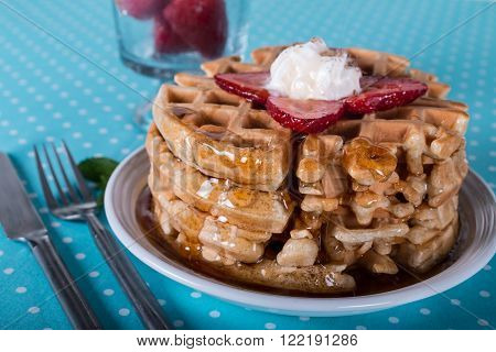 Tall stack of Belgian waffles with thick oozing syrup fresh berries and mint garnish