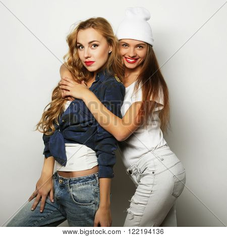 lifestyle portrait of two pretty teen girlfriends smiling and ha