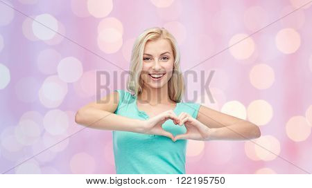 gesture and people concept - smiling young woman or teenage girl showing heart shape made of fingers over pink holidays lights background