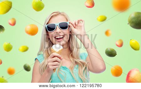 summer, junk food and people concept - young woman or teenage girl in sunglasses eating ice cream over green background with fruits