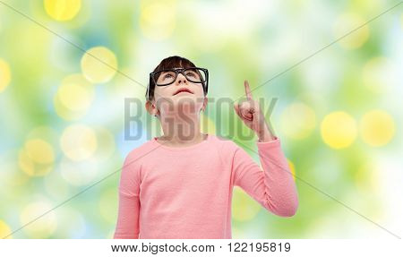 childhood, school, education, vision and people concept - happy little girl in eyeglasses pointing finger up over green lights background