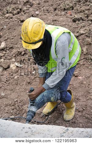MALACCA, MALAYSIA - FEBRUARY 23, 2016: Construction workers make holes at the concrete wall by drilling it using drilling machine.