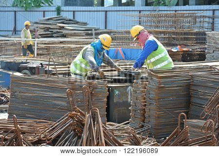 SELANGOR, MALAYSIA - JANUARY 23, 2016: Construction workers working at the steel bar bending yard in the construction site.