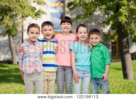 childhood, fashion, friendship and people concept - group of happy smiling little children hugging over summer campus background