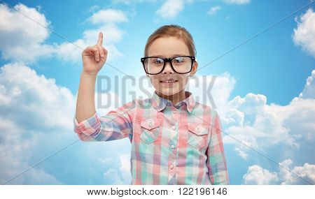 childhood, school, education, vision and people concept - happy little girl in eyeglasses pointing finger up over blue sky and clouds background