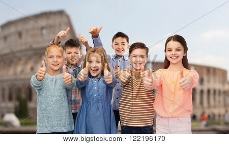 childhood, travel, tourism, gesture and people concept - happy smiling children showing thumbs up over coliseum in rome