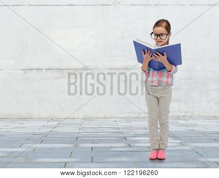childhood, school, education, vision and people concept - happy little girl in eyeglasses reading book over urban concrete background