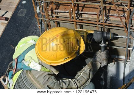 MALACCA, MALAYSIA - FEBRUARY 23, 2016: Construction workers make holes at the concrete wall by drilling it using drilling machine