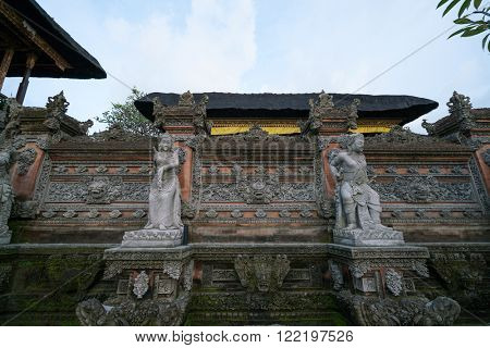 The wall of the Pura Padang Kerta Temple in Ubud, Bali Island is adorn with stone carvings.