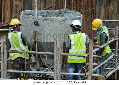 SELANGOR, MALAYSIA - DECEMBER 12, 2015: A group of construction workers pouring concrete using concrete bucket into the pile cap form work at the construction site.