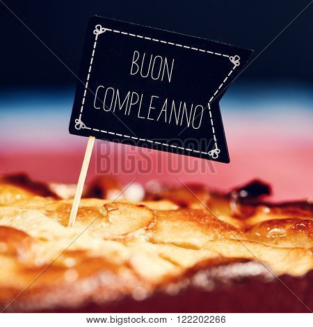 closeup of a black flag-shaped signboard with the text buon compleanno, happy birthday in italian topping a cake