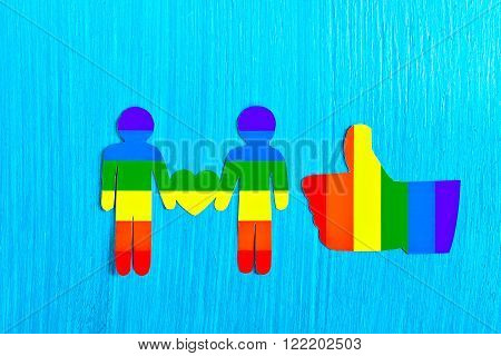 Two people from a paper heart in hands. Like gesture, thumbs up. Flag Colors of homosexuality. the relationship between the two men. Same-sex love. Homosexual relationships. Minorities. Logo LGBT.