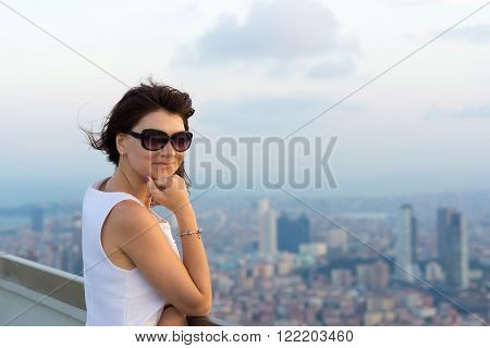 smiling young woman with background of big city
