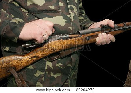 Fragment loading rifle Mosin - chambering a cartridge in the chamber a man dressed in a camouflage uniform on a black background