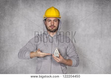 Worker Holds A House In His Hand