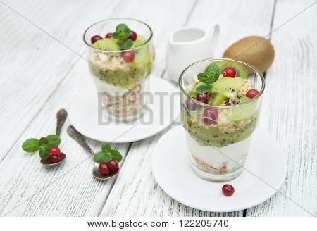 Healthy breakfast with kiwi yogurt muesli and cranberry. Layered cream dessert