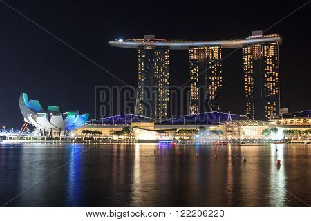 Singapore, Singapore - May 18, 2015: Marina Bay Sands hotel at night with light and laser show in Singapore. The luxury resort is a landmark in Singapore. The laser show starts every evening.