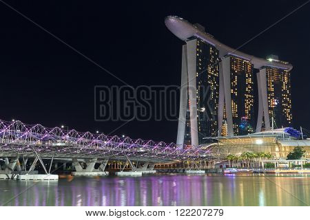 Singapore, Singapore - May 18, 2015: Helix bridge and hotel Marina Bay Sands in Singapore at night. The hotel is a luxury resort famous for its infinity swimming pool and a landmark in Singapore.