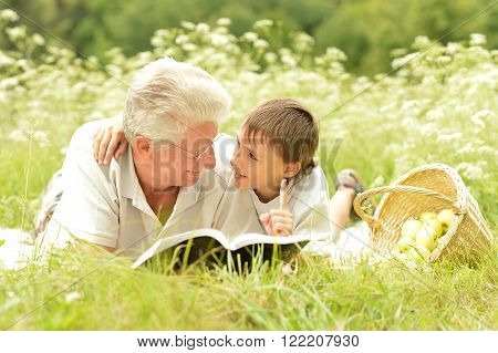Grandfather and his grandson reading book outdoors.