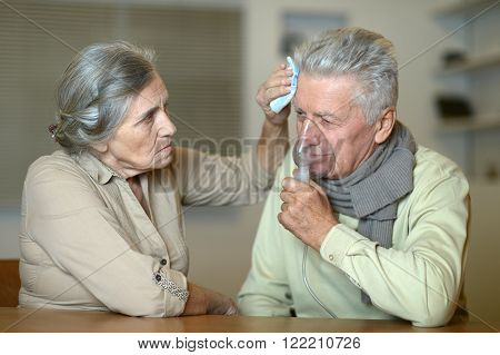 Portrait of ill senior couple with inhaler