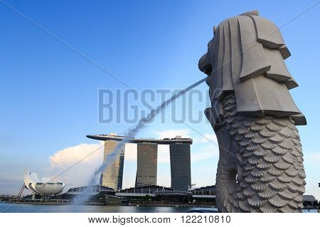 Singapore, Singapore - May 18, 2015: The Merlion statue in the foreground and  Marina Bay Sands hotel in the background. The Merlion is a traditional creature with a lions head and a body of fish. Both are landmarks in Singapore.