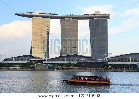 Singapore, Singapore - May 17, 2015: The hotel Marina Bay Sands at the Marina Bay in Singapore with a boat. Its a luxury resort famous for its casino and infinity swimming pool. The hotel is one of the landmarks and tourist attractions in Singapore.