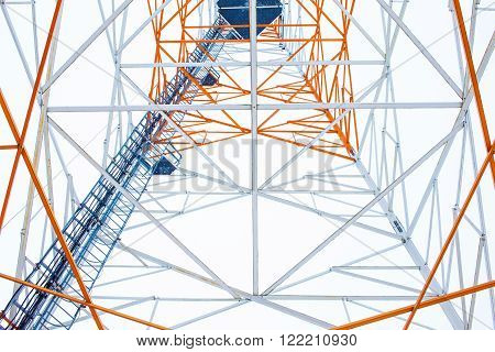 metal constructions tower on a white background. ladders, poles and metal tower closeup. bottom view