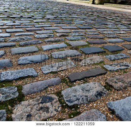 Close up of old worn out brick paving blocks separated by stones in road