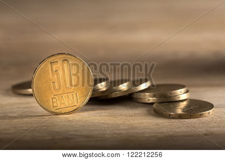 Stacks of Romanian fifty bani coins on wooden table with selective focus