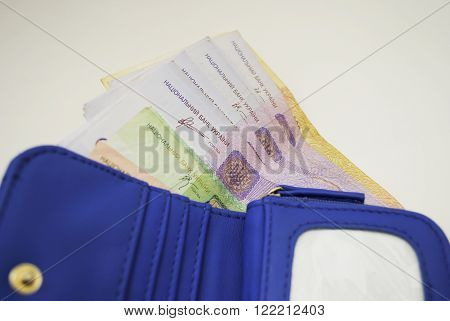 blue wallet with bills Ukrainian hryvna on the table