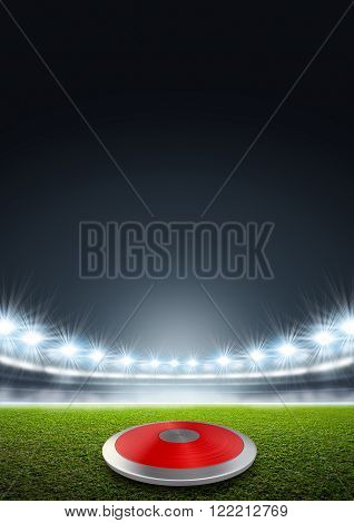 A discus in a generic stadium resting on an unmarked green grass pitch at night under illuminated floodlights