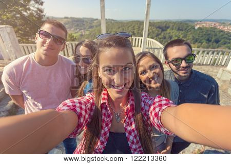 Group of friends having fun and taking selfie in the park. Friendship - lifestyle concept.