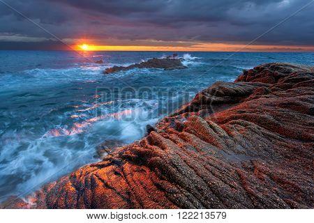 Beautiful sunrise on Greek coast of Aegean sea with holy mountain Athos in background. Chalkidiki Greece.