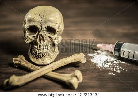 Still life human skull and crossbones with syringe healthcare and medical drugs addition concept