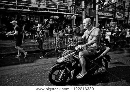 KO SAMUI THAILAND - APRIL 13: Unidentified tourist on a bike in a water fight festival or Songkran Festival (Thai New Year) on April 13 2014 in Chaweng Main Road Ko Samui island Thailand.