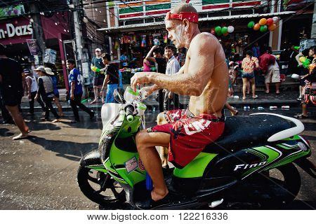 KO SAMUI THAILAND - APRIL 13: Unidentified dirty wet biker in a water fight festival or Songkran Festival (Thai New Year) on April 13 2014 in Chaweng Main Road Ko Samui island Thailand.