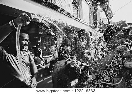 KO SAMUI, THAILAND - APRIL 13: Unidentified man hosing people on Songkran Festival (Thai New Year) on April 13, 2014 in Chaweng Main Road, Ko Samui island, Thailand.