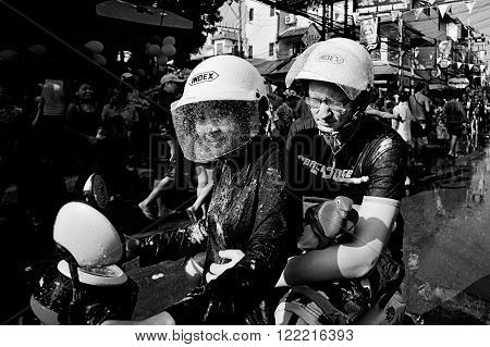 KO SAMUI, THAILAND - APRIL 13: Unidentified wet people on a bike on Songkran Festival (Thai New Year) on April 13, 2014 in Chaweng Main Road, Ko Samui island, Thailand.