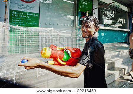 KO SAMUI, THAILAND - APRIL 13: Unidentified man with a watergun in a water fight festival or Songkran Festival (Thai New Year) on April 13, 2014 in Chaweng Main Road, Ko Samui island, Thailand.