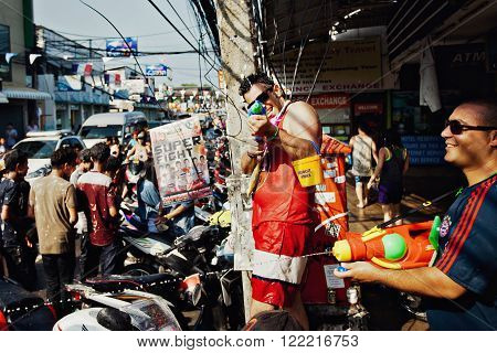 KO SAMUI, THAILAND - APRIL 13: Unidentified man shooting water at the camera on Songkran Festival (Thai New Year) on April 13, 2014 in Chaweng Main Road, Ko Samui island, Thailand.