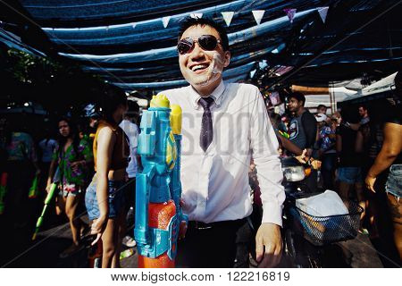 KO SAMUI, THAILAND - APRIL 13: Unidentified man with a watergun on Songkran Festival (Thai New Year) on April 13, 2014 in Chaweng Main Road, Ko Samui island, Thailand.