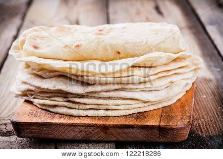 Stack of homemade wheat tortillas on wooden table