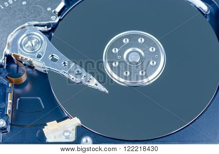 Blue toned close up shot of a Harddisk drive. Shows the head and the storage plates.