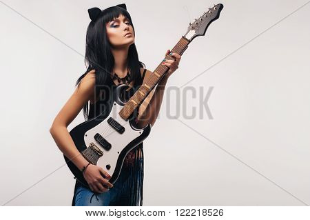 Beautiful girl with an electric guitar isolated on white. Guitar lessons